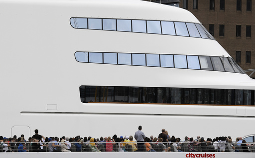 Passengers on a river cruise boat pass superyacht