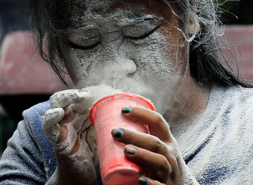 A girl's face is covered by a white powder after blowing on it, while participating in a game during a religious festival honouring patron saint Santa Rita de Cascia in Paranaque city