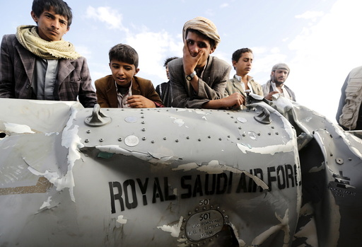 People stand by part of a Saudi fighter jet found in Bani Harith district north of Yemen's capital Sanaa