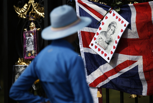 A passer-by looks at tributes left in honor of the late Princess Diana outside Kensington Palace on the 19th anniversary of her death in Paris after a car crash
