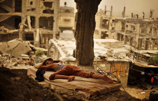 Palestinian boy sleeps on a mattress inside the remains of his family's house that witnesses said was destroyed by Israeli shelling during a 50-day war in 2014 summer during a sandstorm in Gaza