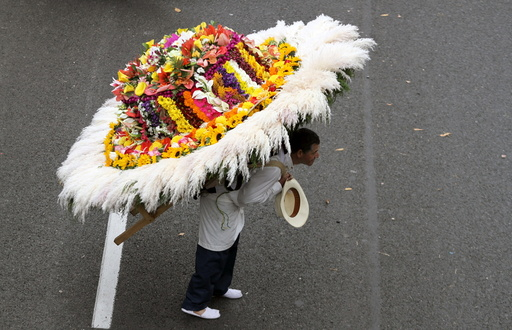 A man wearing a floral arrangement on his back takes part in the annual flower parade, in which flower growers known as