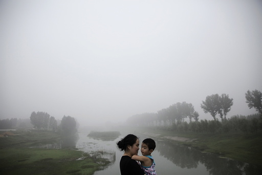 A woman holds a child as travellers wait for the highway from Beijing to China's Hebei Province to reopen after in was closed due to low visibility, on a heavy polluted morning