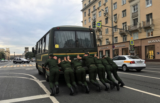 Russian servicemen push a bus along an avenue in Moscow