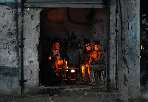 People warm themselves around a fire inside a shop in the Syrian rebel-held town of al-Rai