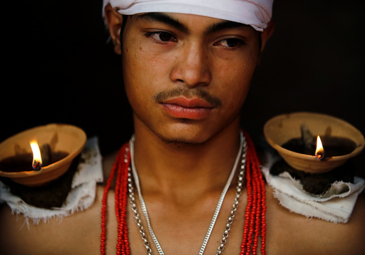 A devotee sits with lit oil lamps on his shoulders while offering prayers during
