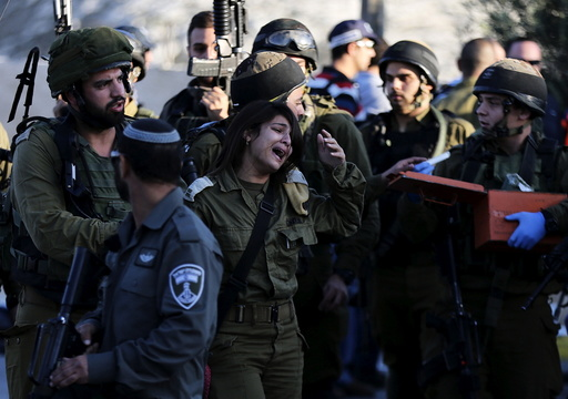 Israeli female soldier reacts at the scene where a Palestinian stabbed and killed an Israeli soldier at a petrol station before he was shot dead by soldiers near the West Bank village of Khirbit Al-Misbah