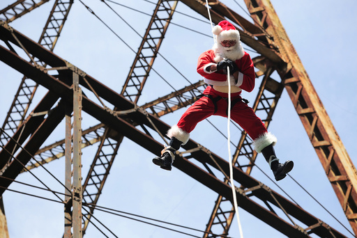 Guatemalan firefighter Chacon, wearing a Santa Claus outfit, rappels down the Belize bridge to give toys to children living under the bridge, in Guatemala City