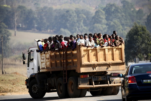 Maidens riding in the back of a dump truck arrive ahead of the last day of the Reed Dance at the Ludzidzini royal palace in Swaziland