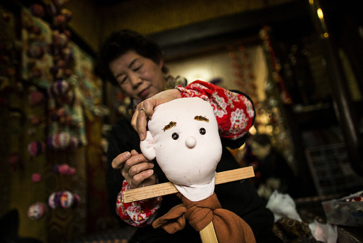 Tsukimi Ayano sows an ear onto a scarecrow in her house in the mountain village of Nagoro