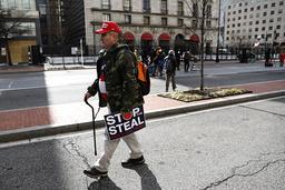 En enslig Trump-tilhenger gikk onsdag gatelangs i Washington med en plakat som hevdet at Joe Biden og Demokratene «stjal» valget 3. november. Foto: AP / NTB