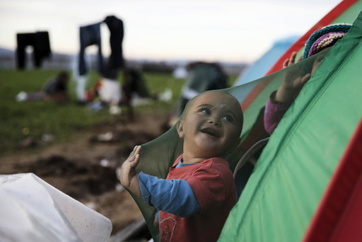 A migrant who is waiting to cross the Greek-Macedonian border, plays in his tent at a makeshift camp near the village of Idomeni, Greece