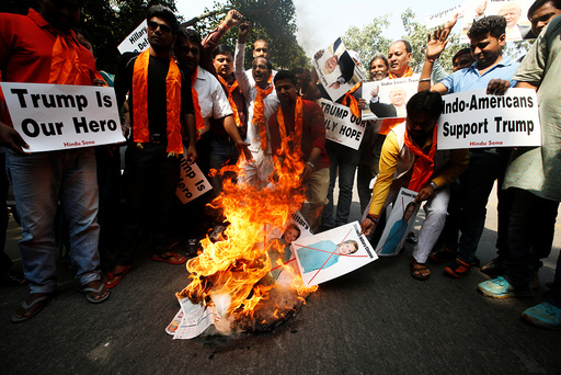 Members of Hindu Sena burn posters of U.S. Democratic presidential nominee Clinton during a protest against what they say is Clinton sabotaging Republican U.S. presidential nominee Trump's election campaign, in New Delhi