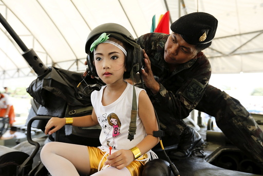 Girl has her helmet adjusted on the top of a tank during the Children's Day celebration at a military facility in Bangkok