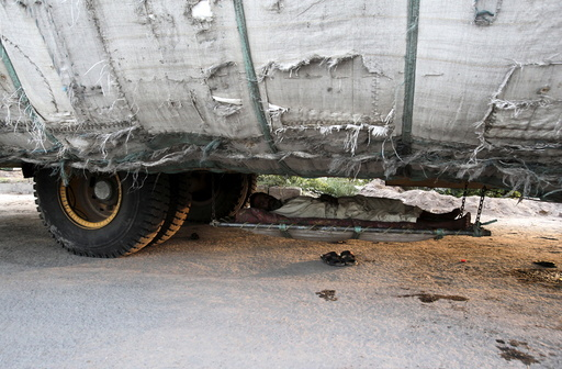 A man sleeps under a supply truck along a roadside in Lahore