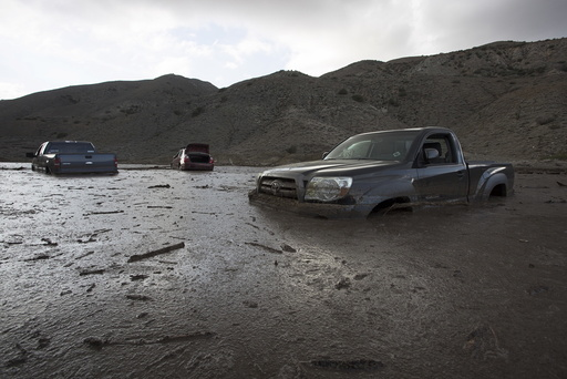 Cars and trucks remain mired in mud and debris on State Route 58 near Tehachapi