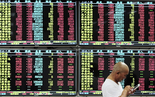 An investor looks at his mobile phone in front of electronic screens showing stock information at a brokerage house in Jiujiang