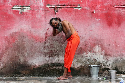 A Sadhu or a Hindu holy man bathes before registering for the annual pilgrimage to the Amarnath cave shrine, at a base camp in Jammu