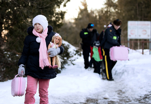 A young girl carries her doll and suitcase as her family that claimed to be from Turkey are met by Royal Canadian Mounted Police (RCMP) officers after they crossed the U.S.-Canada border illegally leading into Hemmingford, Quebec Canada