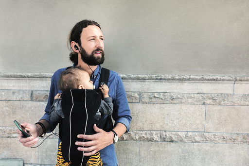 Mid adult father listening music while carrying baby in carrier against wall