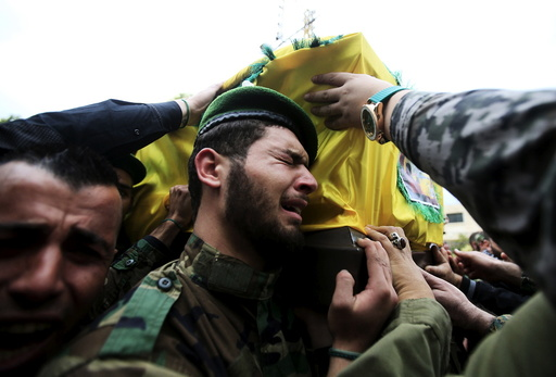 A Lebanon's Hezbollah member reacts as he carries with others the coffin of his comrade, Mohamad Sfawi, who was killed fighting alongside Syrian army forces in Syria, during his funeral in Qnarit village, southern Lebanon