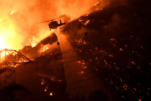 A Los Angeles County fire helicopter makes a night drop while battling the so-called Fish Fire above Azusa, California