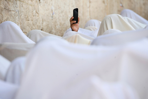 A Jewish worshipper uses his mobile phone to record worshippers who are covered in prayer shawls as they recite the priestly blessing at the Western Wall in Jerusalem's Old City during the Jewish holiday of Sukkot