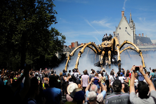 People look at the giant mechanical spider Kumo Ni created by La Machine production company during its presentation in Nantes