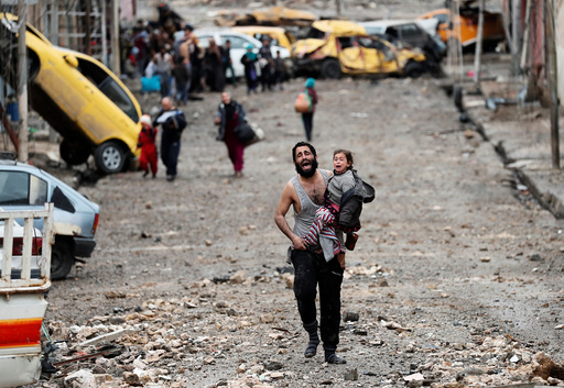A man cries as he carries his daughter while walking from an Islamic State-controlled part of Mosul towards Iraqi special forces soldiers during a battle in Mosul