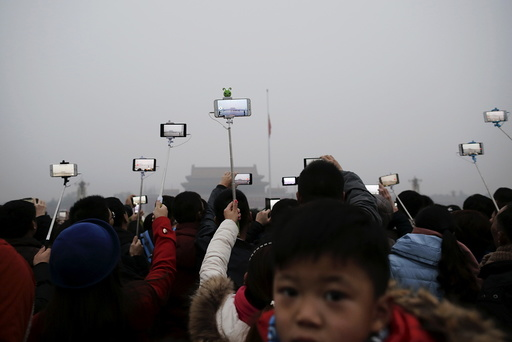 People film with their cameras during a flag-raising ceremony amid heavy smog at the Tiananmen Square, after the city issued its first ever