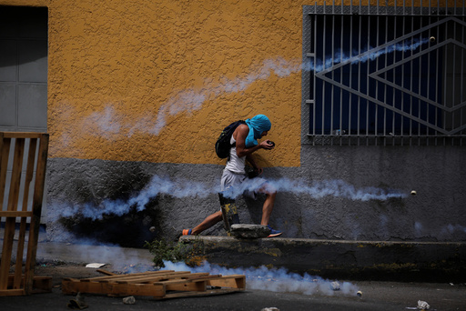 A demonstrator runs away from tear gas during a rally called by health care workers and opposition activists against Venezuela's President Nicolas Maduro in Caracas