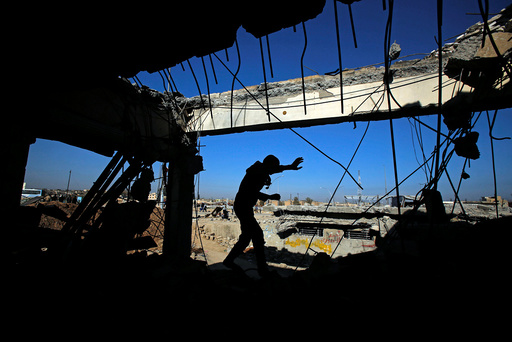 An Iraqi runs through a destroyed building as Iraqi forces battle with Islamic State militants, in western Mosul