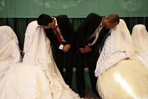 Brides speak to their grooms during a mass wedding ceremony in Amman