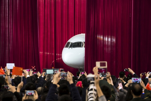 People take pictures and videos as the first C919 passenger jet is pulled out from behind a curtain during a news conference in Shanghai