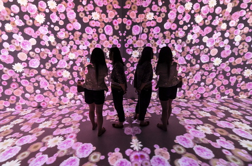 Women are reflected in a mirror as they look at flowers being projected onto the wall and the floor of a room at a shopping mall in Shanghai