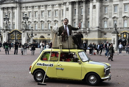 British comedian Atkinson, in character as 'Mr Bean', poses on a Mini car, during a publicity event near Buckingham Palace in central London