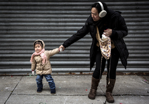 A child pulls her mother away from Chinese Lunar New Year celebrations in New York