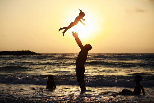 A Muslim man plays with his daughter along the shore of the Mediterranean Sea during the Muslim holiday of Eid al-Fitr, in Ashkelon