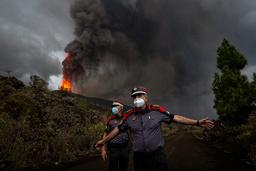 En politimann beordrer pressefolk bort fra vulkanen på La Palma på Kanariøyene. Et nytt utbrudd fredag førte til at en rekke flygninger ble innstilt. Foto: AP / NTB