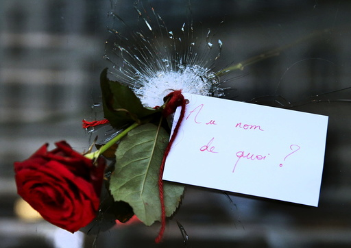 A rose placed in a bullet hole in a restaurant window the day after a series of deadly attacks in Paris