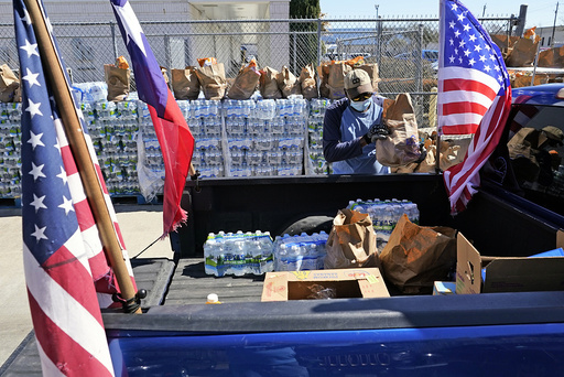 Food and water are loaded into the back of a pickup truck at a distribution site Monday, Feb. 22, 2021, in Houston. The city's boil water notice has been rescinded however many residents lack water at home due to broken pipes. (AP Photo/David J. Phillip)