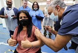 Legen Anil Mehta får en vaksinedose i London for å markere at hennes legekontor har satt 10.000 vaksinedoser så langt. Foto: Frank Augstein / AP / NTB