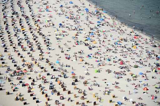 People sitting in beach chairs enjoy the hot sunny weather at the Baltic Sea resort Travemuende