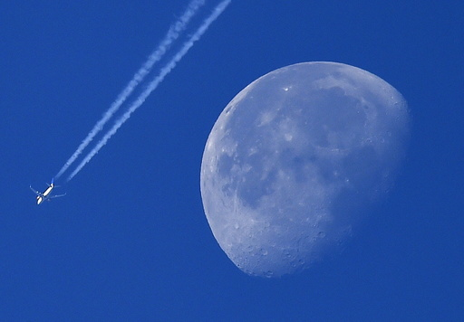 A passenger plane is seen with the moon behind over west London, Britain