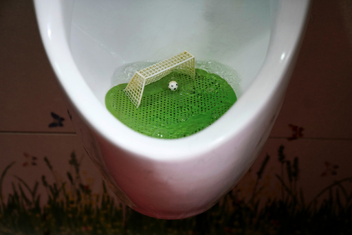 An urinal filter designed in the likeness of a soccer field with a goal post and a ball is pictured in a men's room of a public toilet in Shanghai