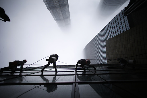 Workers clean the exterior of Shanghai's skyscraper Shanghai World Financial Center next to Shanghai Tower and Jin Mao Tower in Shanghai's financial district of Pudong