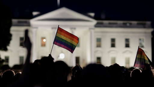 A rainbow flag is held up during a vigil after the worst mass shooting in U.S. history at a gay nightclub in Orlando, Florida, in front of the White House in Washington