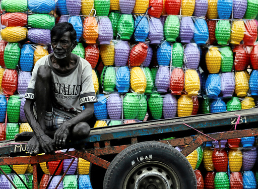 A man rests on his cart after unloading plastic jugs near a shop at a main market in Colombo