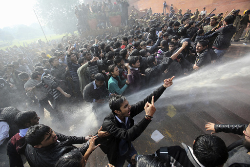 Demonstrators shout slogans as police use water cannons to disperse them near the presidential palace during a protest rally in New Delhi