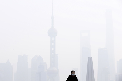 A woman wearing a face mask stands in front of financial district of Pudong amid heavy smog in Shanghai